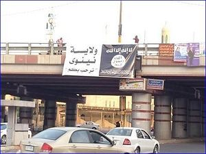 "An ISIS flag hangs from a bridge in Mosul. On the left it says ""Nineveh Governorate welcomes you"" and on the right it says ""There is no God but Allah."""