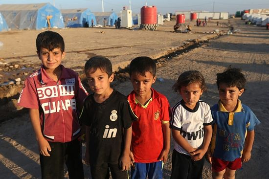 Iraqi children pose for a picture at a camp for displaced Iraqis who fled from Mosul and other towns, in Khazer area outside Irbil, northern Iraq, Sunday, June 22. Sunni militants on Sunday captured two border crossings, one along the frontier with Jordan and the other with Syria, security and military officials said. (Hussein Malla/The Associated Press)