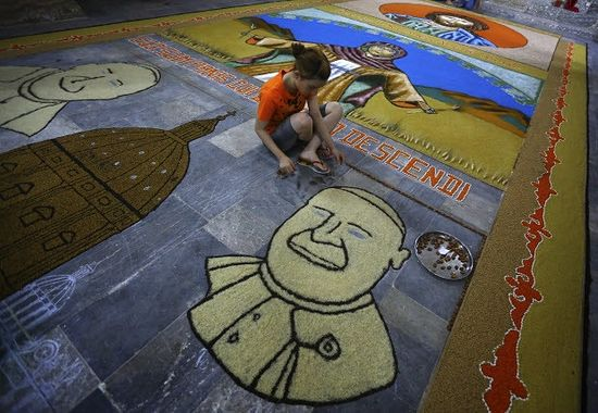 An Iraqi child works on a temporary mosaic of Pope Francis' face made from the area's produce, including wheat, beans and lentils to commemorate an upcoming harvest feast, at the Chaldean Church of the Virgin Mary of the Harvest, in Alqosh, a village of some 6,000 inhabitants about 50 kilometers (31 miles) north of Mosul, northern Iraq. (AP Photo)