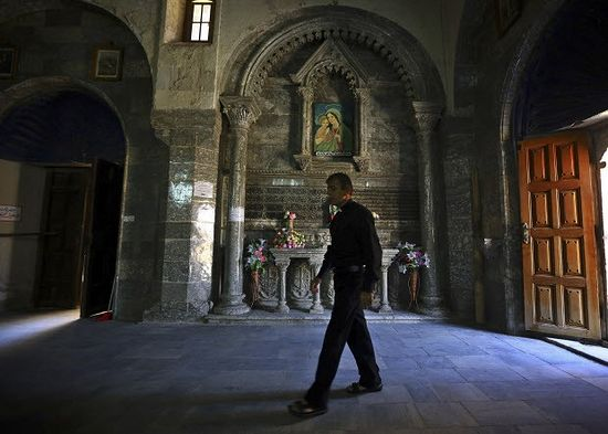 Friar Gabriel Tooma enters the Chaldean Church of the Virgin Mary of the Harvest, set in the seventh century Saint Hormoz monastery built into a hill overlooking Alqosh, a village of some 6,000 inhabitants about 50 kilometers (31 miles) north of Mosul, northern Iraq. (AP Photo)