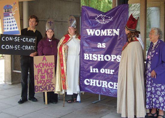 Надписи на плакатах: «Ос-вя-тить! Ос-вя-тить!», «Место женщины – в доме епископов», «Женщины как епископы в нашей церкви»
