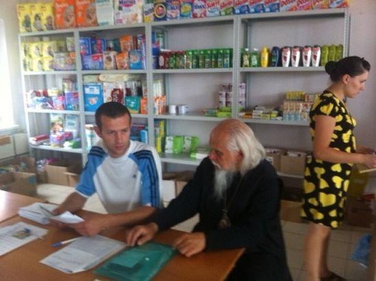 Епископ Пантелеимон беседует с металлургом Евгением из Донецка на епархиальном складе в Ростове-на-Дону.