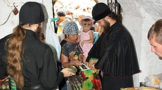 Монахи раздают продукты нуждающимся.