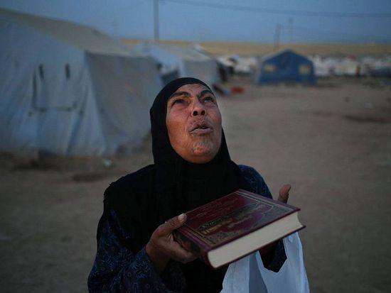 Мусульманка, сбежавшая из Мосула, молится, сжимая в руках Коран. Hussein Malla/AP