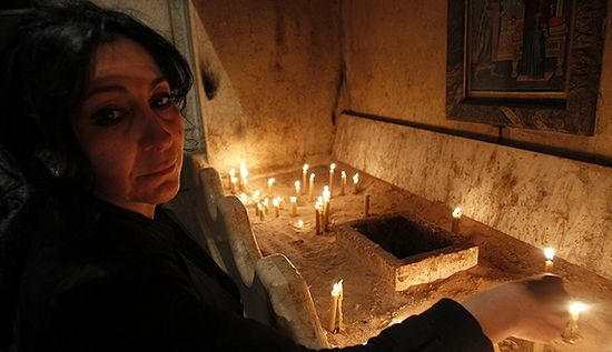 Iptisam, an Iraqi Christian woman, lights candles for victims of the attack on Our Lady of Salvation church of Baghdad, during a mass at an Orthodox church in Amman, November 7, 2010. (photo by REUTERS/Ali Jarekji)