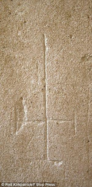 Перевернутый крест на внутренней стене, высеченный сатанистами. Фото: Род Киркпатрик / F Stop Press