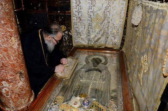 Патриарх молится у гробницы прп.Афанасия Афонского