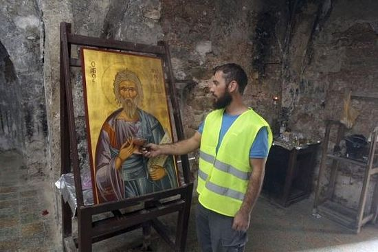 A construction worker lights a candle in front of an icon of the Apostle Andrew in a 15th century chapel at the Apostolos Andreas Monastery in Cyprus.