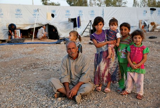A displaced Iraqi man, who fled from the Islamic State violence in Mosul, poses for the camera with his daughters at Baherka refugee camp in Erbil, September 19, 2014.
