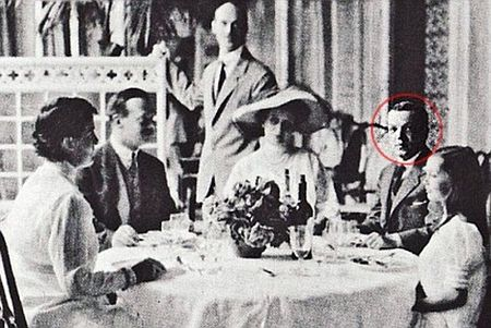 Michael Romanov stands behind his wife Natalya (centre) during a family dinner in Cannes. Nicholas Johnson, circled, sits between her and her daughter Natalya. The child's governess Miss Rata and Andrei Vladimirovich are also at the table