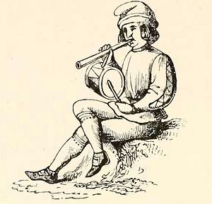 Rustic Christmas minstrel with pipe and tabor.