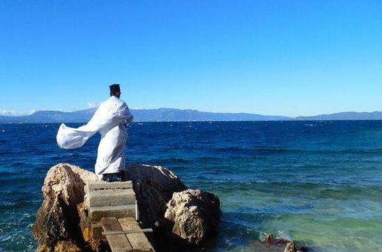 Православный священник освящает море в день Богоявления