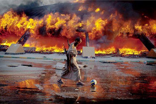 Мятежник играет в футбол на фоне пылающей резиденции М.Каддафи. Фото: Philippe de Poulpiquet, Archive/MAXPPP/ZUMA