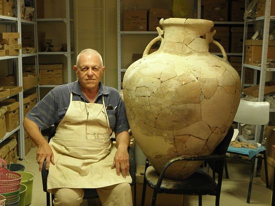 An archaeologist sits next to the large earthenware Cypriot pithoi from 17th century BC that he restored(Tel Burna Archaeological Project)