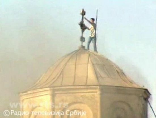 An ethnic Albanian ripping out the cross from a Serb church (Image made from RTS video)