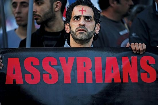 An Assyrian man with a red cross painted on his forehead holds a banner as he walks during a protest of several hundred people in solidarity with Christians abducted in Syria and Iraq, in downtown Beirut, Lebanon, February 28, 2015. HUSSEIN MALLA/AP