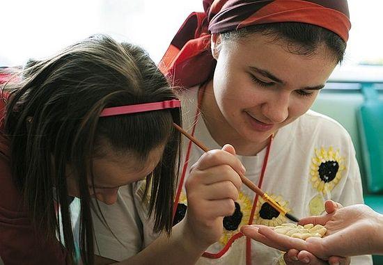 Анечка, младшая дочь, и Люба Соколовы смазывают яйцом украшение для кулича