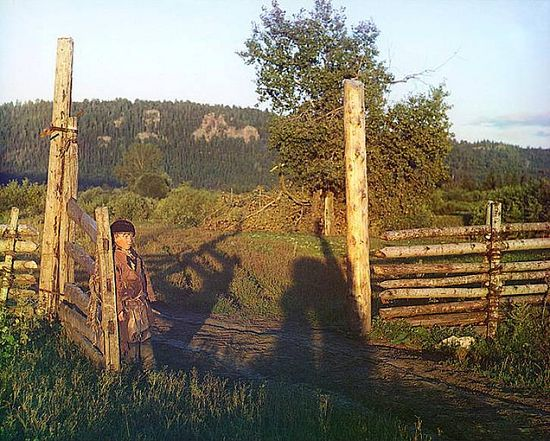 Young boy standing next to a gatepost - 1910