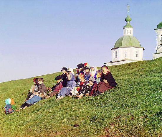 Children sitting on a hill near a church and belltower in the countryside near White Lake in northern Russia - 1909