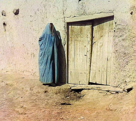Woman in Purdah standing next to a wooden door - between 1909-1915