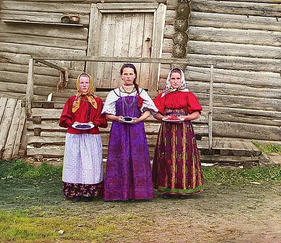 Young women offer berries to visitors to their izbas - traditional wooden houses along the Sheksna River near Kirillov - 1909