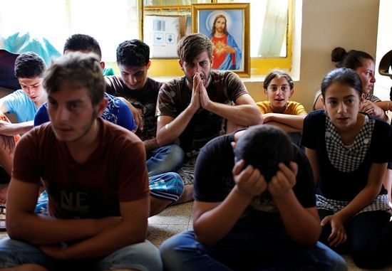 Displaced Iraqi Christians who fled from Islamic State militants in Mosul, pray at a school acting as a refugee camp in Erbil, Iraq, September 6, 2014.