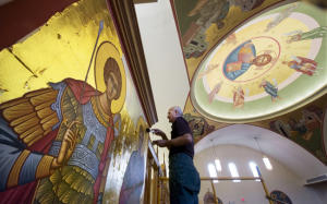 Elias Katsaros applies a thin coat of gold Saturday to a sticky adhesive on an icon in the dome he began many years before at St. John Chrysostom Antiochian Orthodox Church in Springettsbury Township. Saints George and Demetrius, the icons he is working on, were Roman warriors who died for their Christian beliefs.
