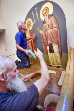 Gary Stump, bottom, of Springettsbury Township and a member of the church, keeps fresh sponges at the ready as the canvas is attached to the wall last week. Now retired, Stump helped with earlier iconography installations at the church and is now able to devote much more of time for this installation. Retired from Verizon, where climbing utility poles was part of the job, Stump said he wasn't afraid of heights. Elias Katsaros, top, began painting iconography at St. John Chrysostom Antiochian Orthodox Church in Springettsbury Township in 1996.
