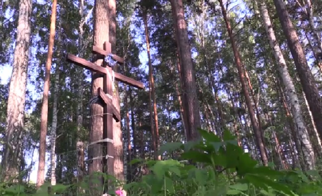 "The damaged memorial cross has been tied and nailed to a nearby tree. What kind of ""human"" desecrates the grave of murdered innocents?"