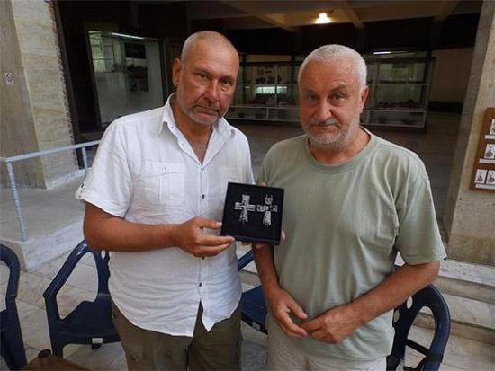 Archaeologists Nikolay Ovcharov (left) and Angel Konakliev (right) with the 14th century lead cross reliquary found in the medieval city of Missionis / Krum's Fortress near Bulgaria's Targovishte. Photo: 24 Chasa daily