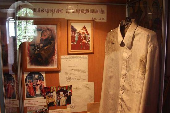 Киот в храме, где хранится рубашка, пробитая ножом убийцы, батюшкин крест, тетрадь с проповедями, открытая на