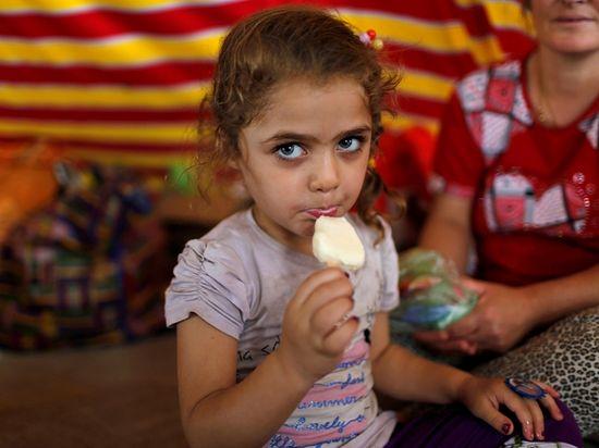 Девочка из Мосула ест мороженое в лагере беженцев в Эрбиле. 2014 г.