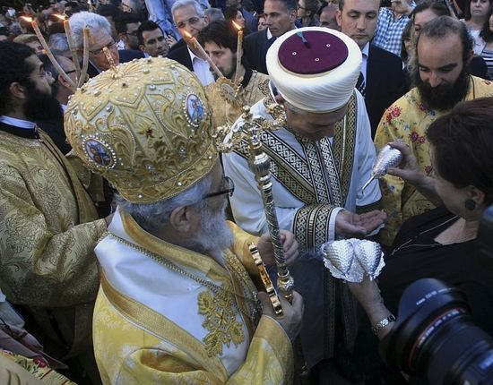 A Greek Orthodox bishop and an Islamic cleric attend a Good Friday liturgy at the Church of St. George Exorinos in Famagusta, northern Cyprus, April 18, 2014. Hundreds of Greek Orthodox pilgrims, some coming home after 40 years of forced exile, commemorated the crucifixion of Jesus in a rare Good Friday service in northern Cyprus on Friday. Held in this medieval walled city in the Turkish part of the divided island, the ceremony at the 14th-century St. George Extorinos church was the idea of local authorities who invited the faithful from the Greek part of the island to visit.PHOTO: REUTERS / ANDREAS MANOLIS