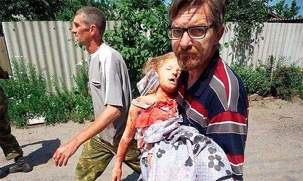 Славянск. Врач несет девочку, погибшую во время артобстрела города на Троицу 2014 г.