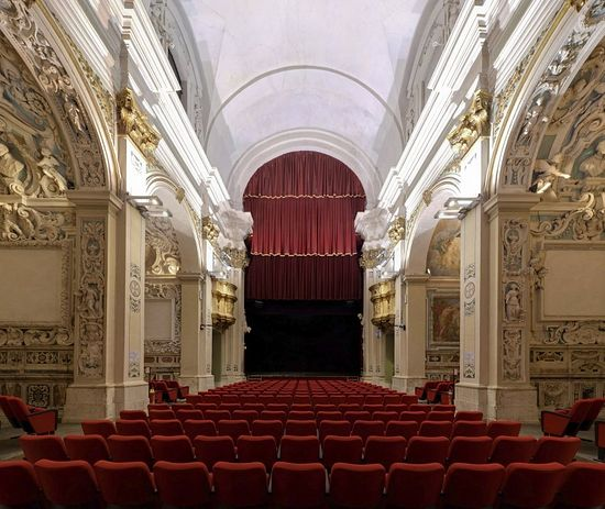Седишта од црвеног плиша испред приказа анђела. Данас је црква Сан Фелипи у Аквилу – позориште. Кад нема довољно новца за рестаурацију цркава оне се у Италији продају у приватну својину