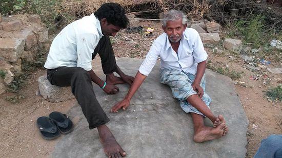 Мужчины играют в начерченную на камне игру