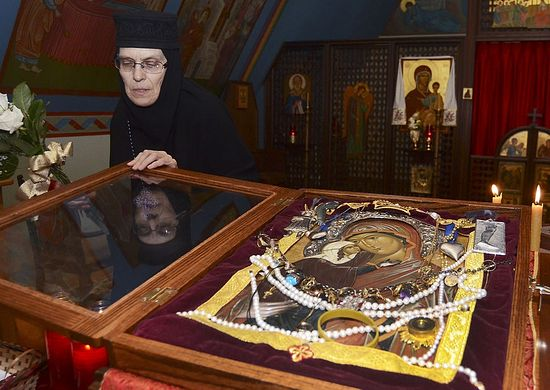 Mother Christophera of the Orthodox Monastery of the Transfiguration in Wayne Township opens a glass case to give a better view of the Icon of St. Anna on Saturday.