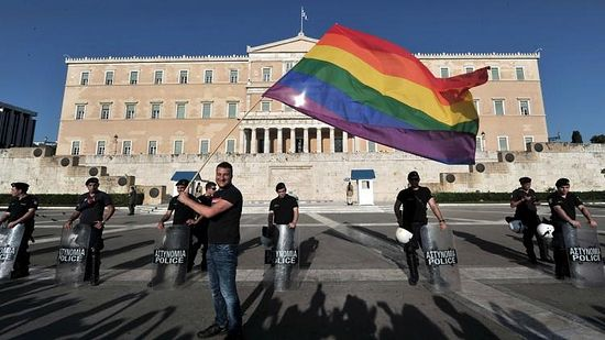 A participant of the Gay Pride event waves a rainbow flag near police protecting the Greek parliament on June 9, 2012.