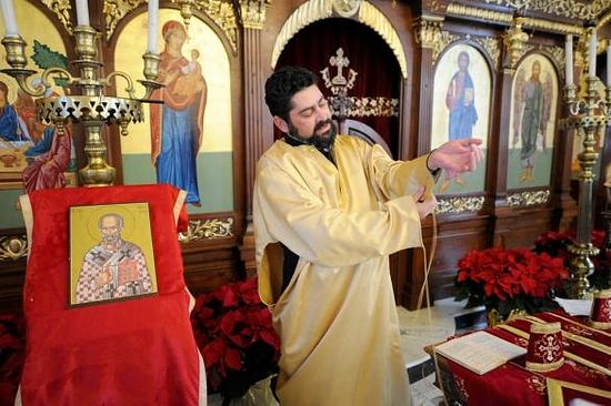 The Rev. Vasile Bitere puts on a sticharion (the large gold robe) at Holy Trinity Greek Orthodox Church. The color gold represents the kingdom of Heaven, he said.