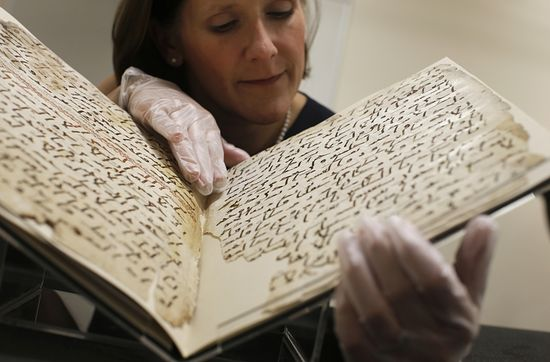 Conservator, Marie Sviergula holds a fragment of a Quran manuscript in the library at the University of Birmingham in Britain, July 22, 2015. A British university said on Wednesday that fragments of a Quran manuscript found in its library were from one of the oldest surviving copies of the Islamic text in the world, possibly written by someone who might have known the Islamic prophet Muhammad. Radiocarbon dating indicated that the parchment folios held by the University of Birmingham in central England were at least 1,370 years old, which would make them one of the earliest written forms of the Islamic holy book in existence.