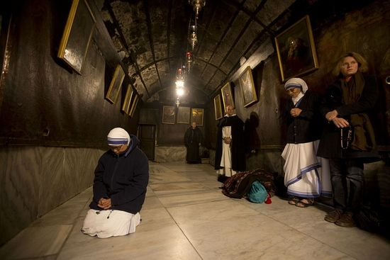 A nun prays inside the Grotto at the Church of the Nativity, traditionally believed by Christians to be the birthplace of Jesus Christ, in the West Bank city of Bethlehem on Christmas Eve, Thursday, Dec.ember 24, 2015 (AP Photo/Majdi Mohammed)