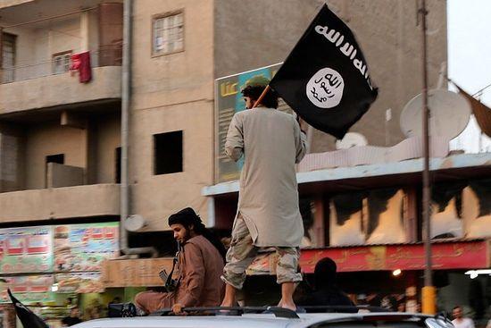 Фото: боевик ИГ с флагом организации в Ракке