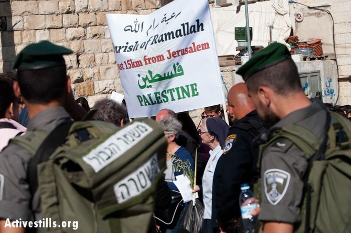 """Israeli soldiers watch as Palestinian Christians in the annual Palm Sunday procession carry signs naming their West Bank communities, all of which are cut off from Jerusalem by the Israeli separation barrier, requiring their residents to obtain special permits to enter, March 24, 2013. Such restrictions have dramatically reduced the number of Palestinians able to participate in religious traditions of any faith in Jerusalem. Palm Sunday is the Christian celebration of Jesus' triumphal entry into Jerusalem as the """"Prince of Peace"""" the week before his crucifixion."""