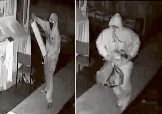 Caught in the act: Two men wearing hoodies or overalls are have been captured on CCTV raiding the Greek Orthodox church, Red Hill.