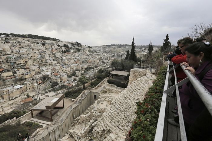Visitors tour at the archaeological site known as the City of David, situated just outside the Old City in East Jerusalem, opposite the mostly Arab East Jerusalem neighborhood of Silwan (L), January 26, 2014.