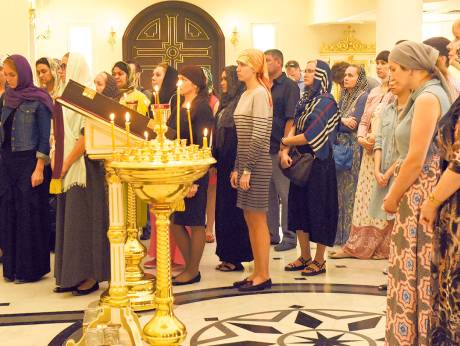 People pray for the victims of Saturday's flydubai plane crash during a service at Sharjah Russian Orthodox Church.