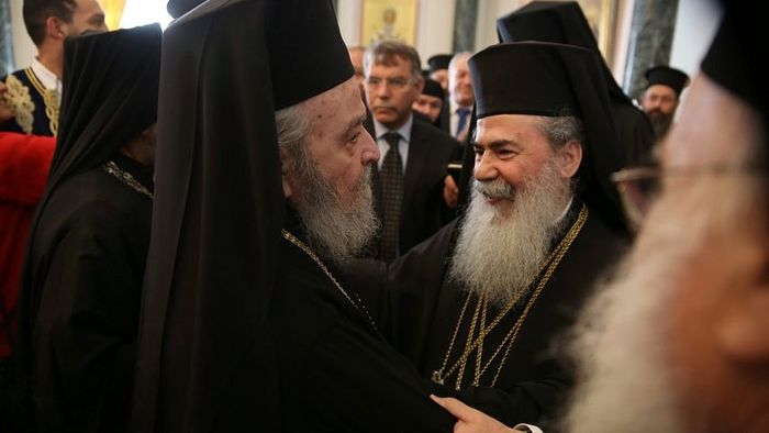 Greek Orthodox Patriarch of Jerusalem Theophilos III (right) is greeted by the former ousted Patriarch of Jerusalem, monk Irenaios, March 22, 2016. AFP
