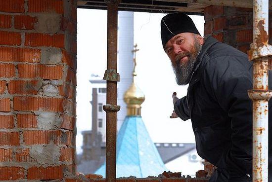 Отец Андрей Галухин показывает временный храм из окна строящегося