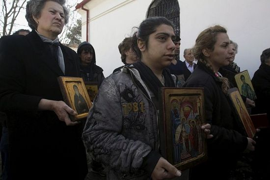 Christian Orthodox Iranian migrants Roya (C) and Sami (R), who live at a makeshift camp for refugees and migrants, hold icons during a mass marking the Sunday of Orthodoxy at the church of the village of Idomeni, Greece, on March 20, 2016.