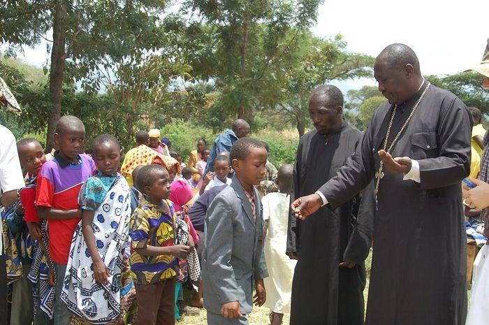Отец Марк Мванги с детьми приюта, которым он руководит вместе со своей матушкой